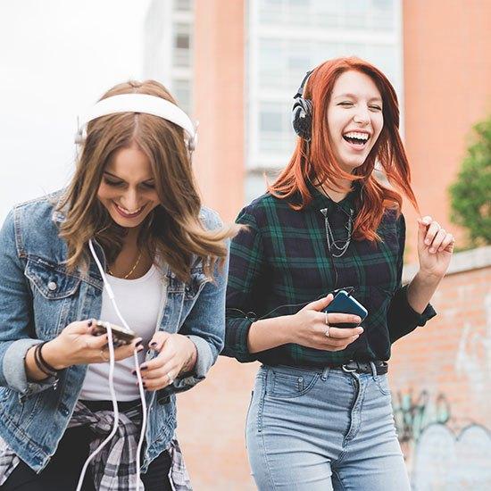 shutterstock_371907745-teenage-girls-laughing-enjoying-music-via-headphones-next-to-graffiti-wall-cropped-for-web